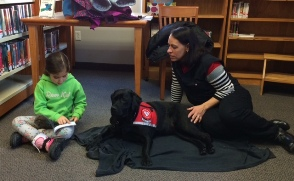 Child reading to Gracie and her person